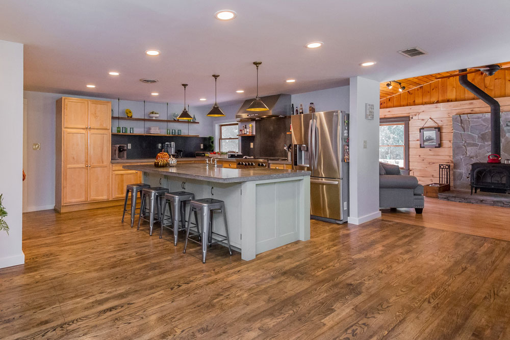 105 grange road in greenfield, ny has a large modern kitchen with concrete counters, farm style sink and high end appliances