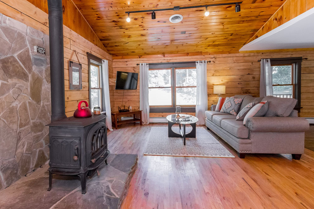 105 grange road in greenfield, ny has hardwood floors, vaulted ceilings and a wood burning stove