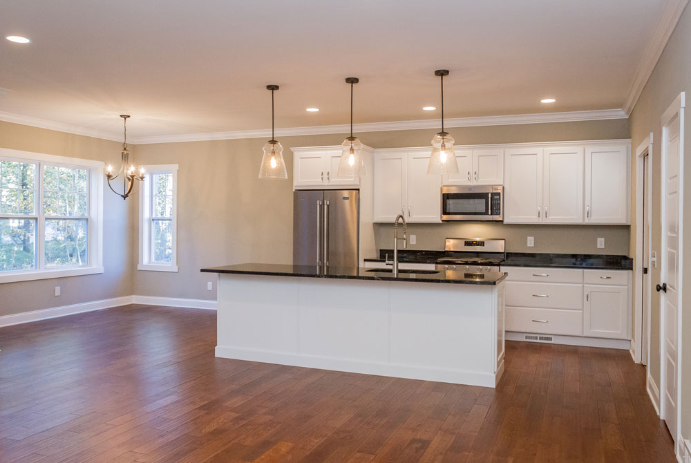 25 Wyndham Way in Milton, NY is a home for sale with an open kitchen with Merillat kitchen cabinets, granite counters and stainless appliances