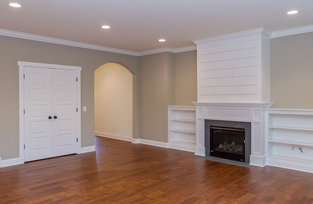 25 Wyndham Way, in Milton, NY is a home for sale with a beautiful living space with gas fireplace surrounded by custom shelving