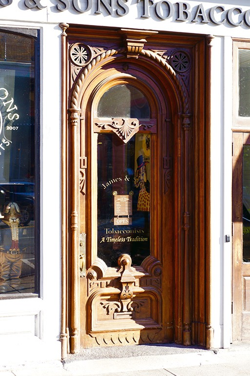 The four-inch thick High Victorian walnut door detailed with intricate carvings of incised lines, rope moldings and an arch at the top, as it is today.