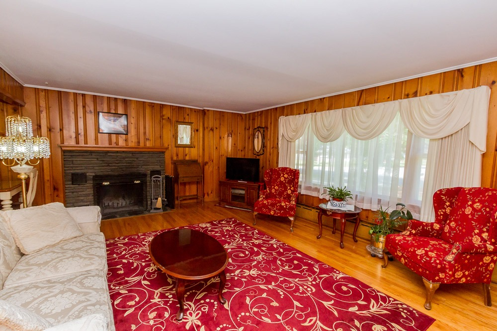 27 Kirby Road, Saratoga Springs, NY is a brick ranch for sale with an oversized 400 sqft living room with hardwood floors and wood burning fireplace