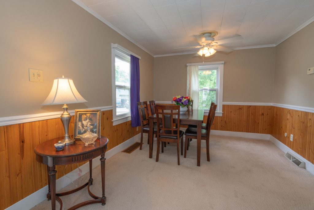 12 Combs Avenue in Hudson Falls, NY is a home for sale with an open dining space with wainscoting and ceiling fan