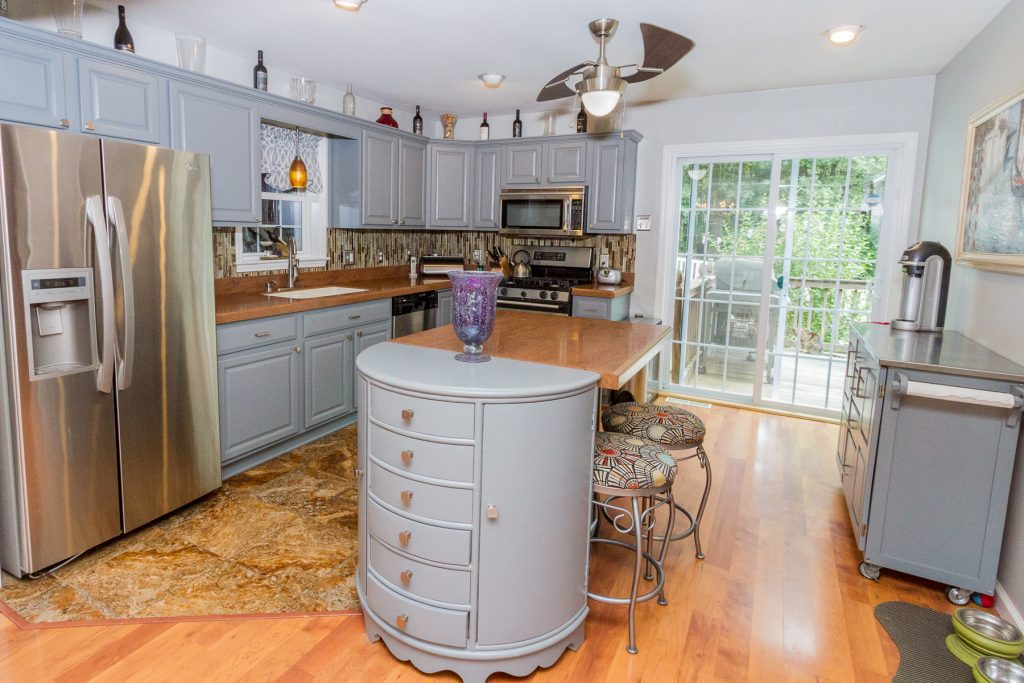 6 Musket Drive is a home for sale in Saratoga, NY with a large kitchen with Corian countertops, island and sliding doors to back deck