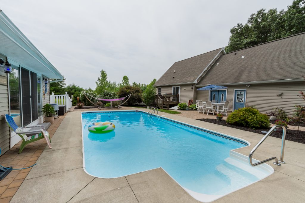 6 Musket Drive, Saratoga, NY is a Cape Cod style home for sale with a heated in-ground pool with large patio and pool house