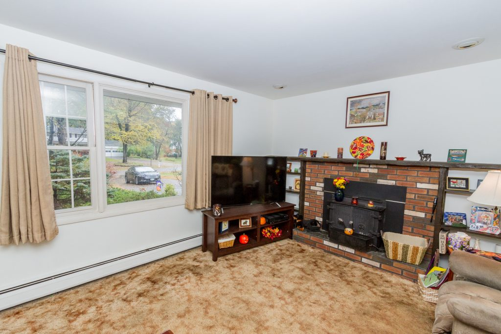 4 Anyhow Lane is a home for sale in Wilton, NY with a living room featuring masonry fireplace with woodstove and a large picture window