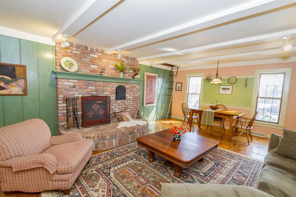 112 North Milton Road has a huge living room with brick fireplace and wide plank reclaimed wood floors throughout