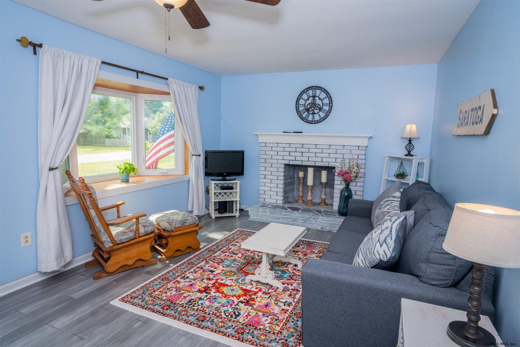 16 Walter Drive Saratoga Springs NY 12866 has a beautiful living room with a wood fireplace and bamboo flooring throughout.