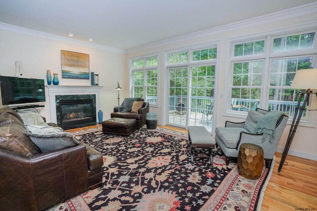 2 Harvest Lane is a home for sale in Wilton New York with a beautiful large sunny living room with gas fireplace & sliders to deck.