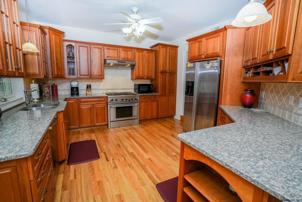 2 Harvest Lane is a home for sale in Wilton New York with a large kitchen with cherry cabinets, stainless appliances, 6 burner stove & granite counters.
