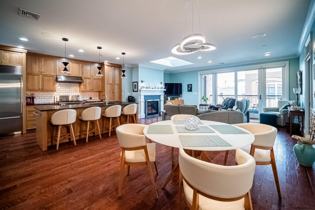 37 Henry Street is a home for sale in Saratoga Springs, NY with an open concept living space with new light fixtures and expansive windows with custom blindsand a newly remodeled fireplace